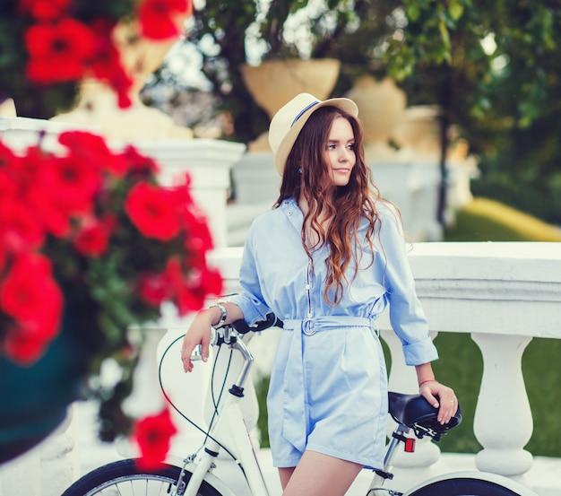 Jeune fille debout près de vélo vintage