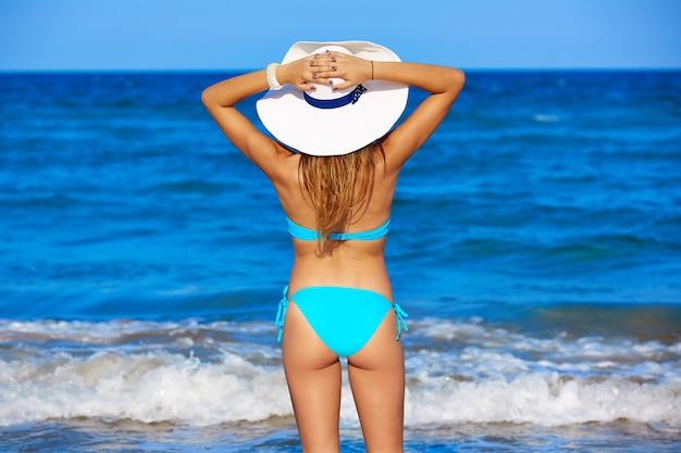 Jeune fille debout en regardant le chapeau de plage de la mer