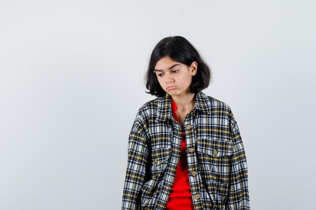 Jeune fille debout, regardant vers le bas et se présentant à la caméra en chemise à carreaux et t-shirt rouge et l'air songeur. vue de face.