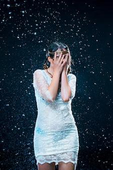 La jeune fille debout sous l'eau courante
