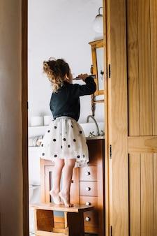 Jeune fille debout sur un tabouret avec brosse à dents regardant miroir