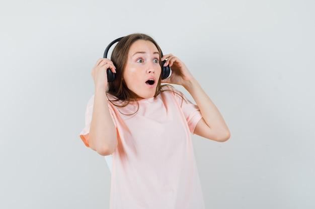 Jeune fille décoller les écouteurs en t-shirt rose et à la surprise