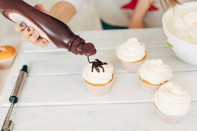 Une jeune fille décore des cupcakes en versant de la crème au chocolat