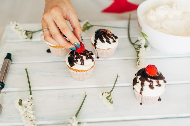 Une jeune fille décore des petits gâteaux avec des baies fraîches et des fleurs