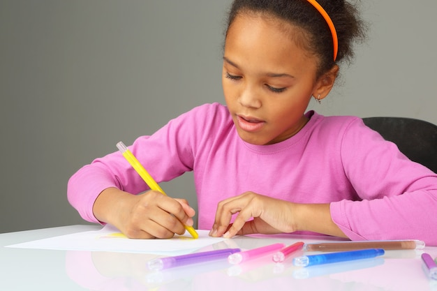La jeune fille dessine un crayon jaune sur du papier blanc