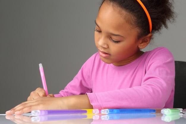 La jeune fille dessine avec des crayons de couleur sur papier