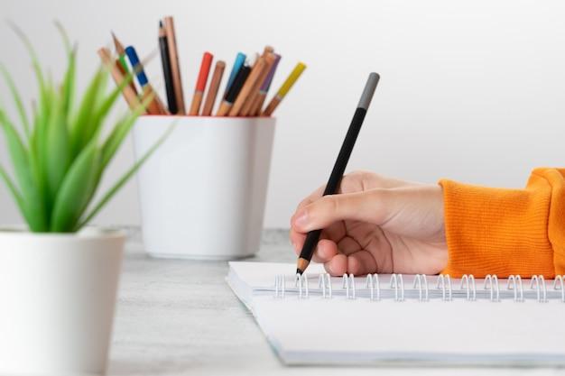 Une jeune fille dessine dans l'album avec un crayon noir. la main se bouchent.