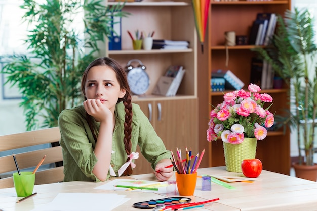 Jeune fille dessine des images à la maison