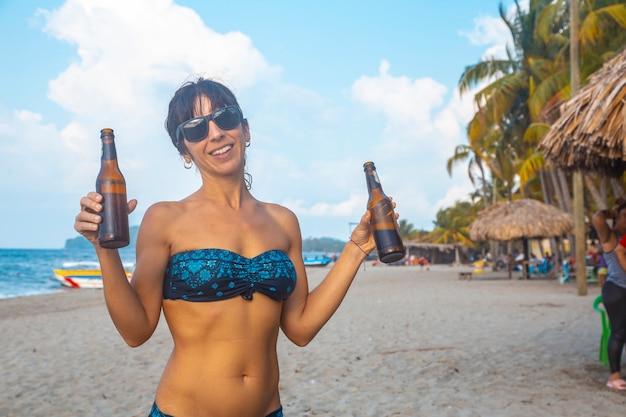 Une jeune fille avec deux bières sur la plage de tela au honduras