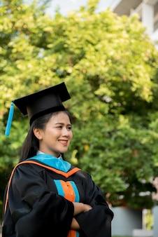 Jeune fille diplômée coiffée d'un chapeau à pompon noir.