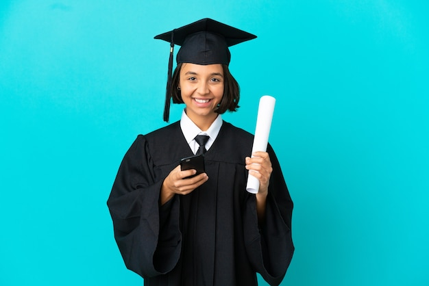 Jeune fille diplômée universitaire sur un mur bleu isolé envoyant un message avec le mobile