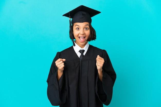 Jeune fille diplômée de l'université sur fond bleu isolé célébrant une victoire en position de vainqueur