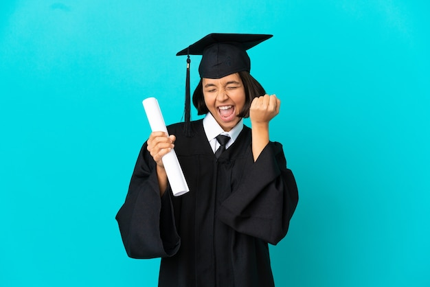 Jeune fille diplômée de l'université sur fond bleu isolé célébrant une victoire