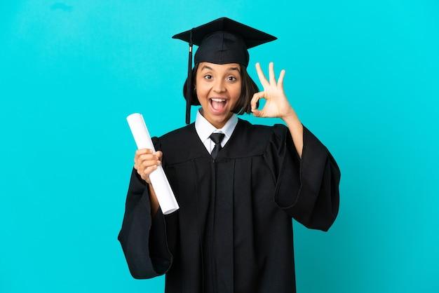 Jeune fille diplômée de l'université sur fond bleu isolé montrant un signe ok et un geste du pouce vers le haut