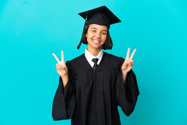 Jeune fille diplômée de l'université sur fond bleu isolé montrant le signe de la victoire avec les deux mains