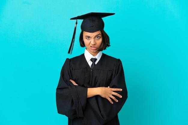 Jeune fille diplômée de l'université sur fond bleu isolé se sentir contrarié