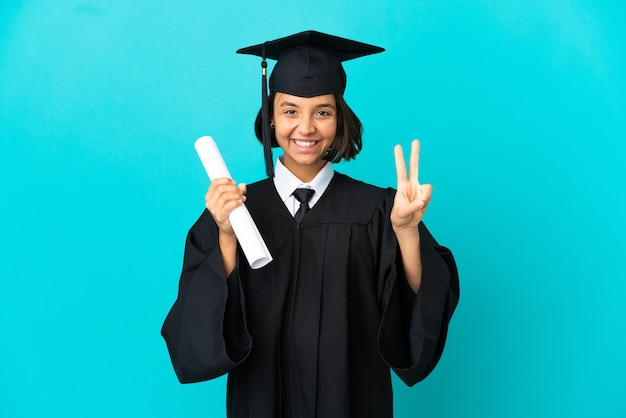 Jeune fille diplômée de l'université sur fond bleu isolé souriant et montrant le signe de la victoire