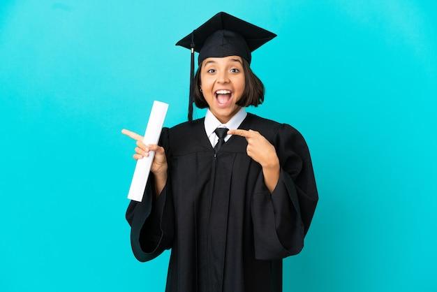 Jeune fille diplômée de l'université sur fond bleu isolé surpris et pointant vers le côté