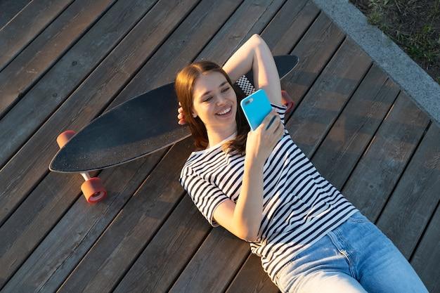 Jeune fille discutant avec des amis en ligne souriant utiliser un smartphone détendu allongé à l'extérieur sur un longboard