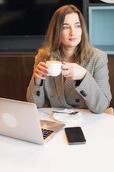 Une jeune fille dodue est assise dans un café en train de boire du café et travaille sur une photo de haute qualité pour ordinateur portable