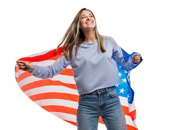 Jeune fille avec un drapeau américain dans ses mains. fête de l'indépendance et patriotisme. isolé sur un blanc