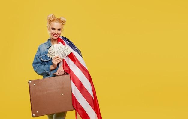 Une jeune fille avec un drapeau américain tient dans ses mains une valise de voyage et des billets en argent. visage joyeux surpris.