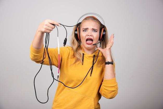 Jeune fille drôle en sweat à capuche jaune posant avec des écouteurs.