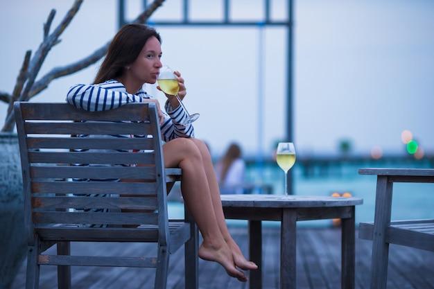 Jeune fille avec du vin blanc au café en plein air en soirée