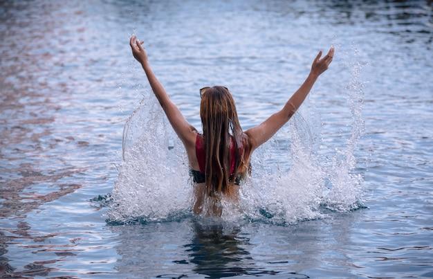 Jeune fille éclaboussant de l'eau dans sa tête dans la piscine.