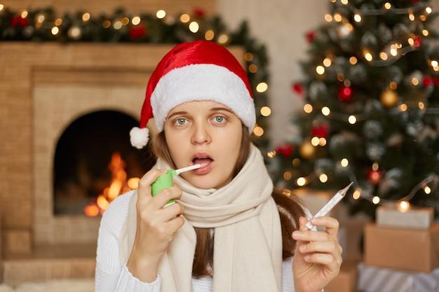 Jeune fille éclabousse dans sa bouche avec un spray de douleur dans la gorge. traitement du rhume, de la grippe, tenant un thermomètre dans les mains, être malade pendant les vacances de noël.