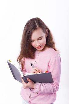 Jeune fille de l'école à prendre des notes dans le planificateur sur mur blanc