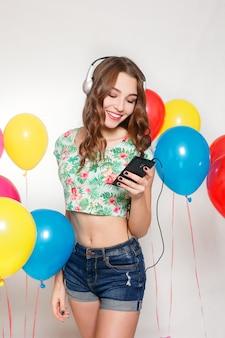 Jeune fille écoutant de la musique avec des écouteurs à côté de ballons