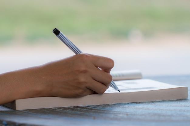 Jeune fille écrit sur un livre