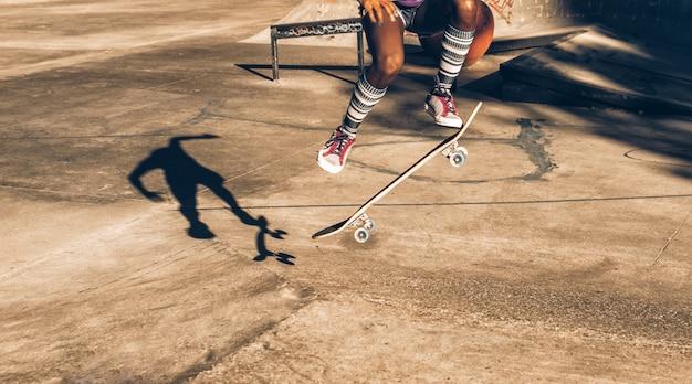 Jeune fille effectuant des tours avec la planche à roulettes dans un skate park