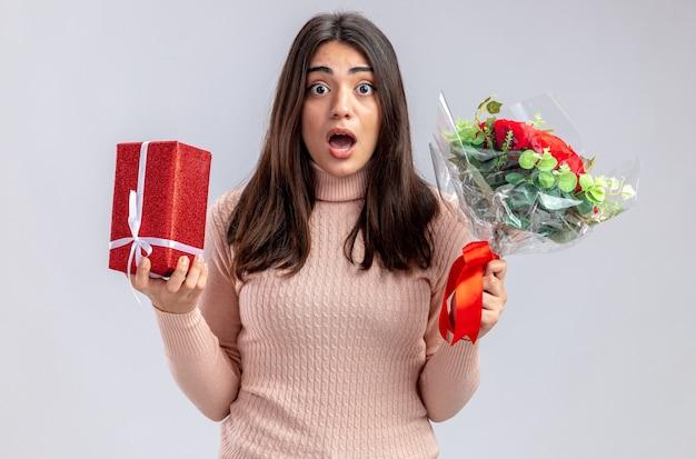 Jeune fille effrayée le jour de la saint-valentin tenant une boîte-cadeau avec bouquet isolé sur fond blanc