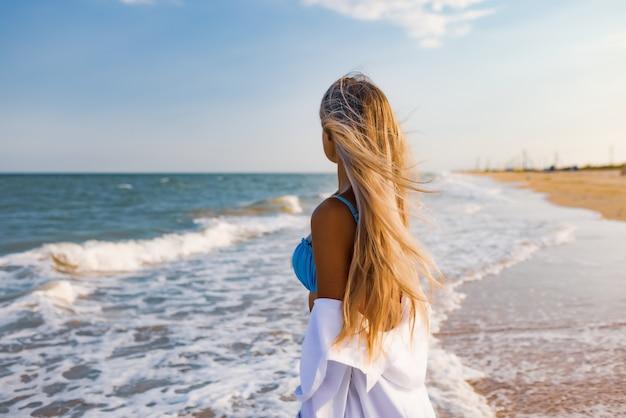 Une jeune fille élancée dans un maillot de bain bleu doux et une chemise blanche, se promène le long d'une large plage de sable près de la mer bleue avec des vagues blanches