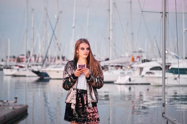 Jeune fille élégante à l'aide de téléphone portable