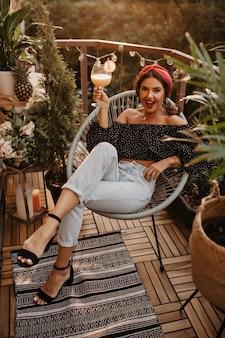 Jeune fille élégante aux cheveux ondulés et bandeau lumineux en haut noir, jeans clairs et talons noirs assis et tenant un cocktail sur une terrasse moderne..