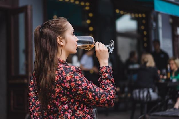 Une jeune fille élégante boit du vin dans un café de rue sur une terrasse d'été. une fille aux cheveux longs apprécie un verre de vin sur une soirée d'été. portrait. fermer
