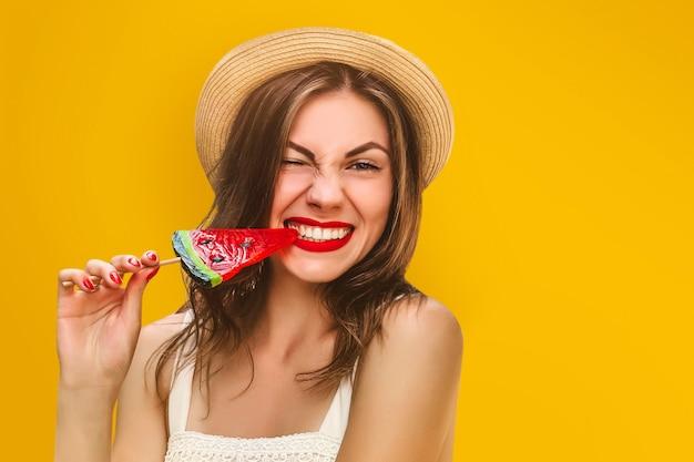 Jeune fille élégante dans un chapeau de paille avec une sucette sur fond jaune