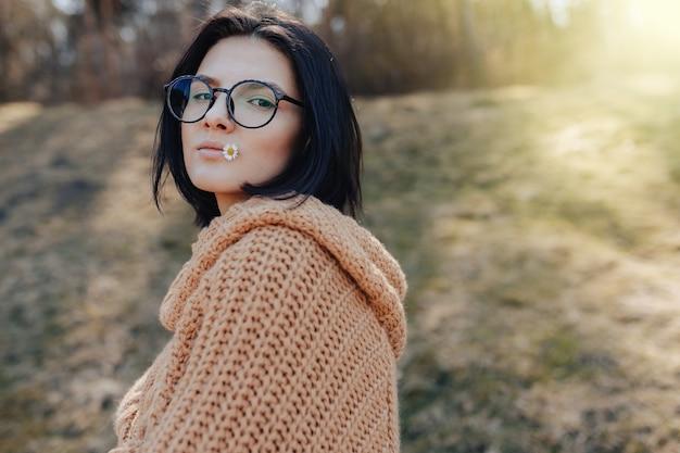Jeune fille élégante sur le fond de la forêt tient une petite marguerite dans sa main et ses lèvres