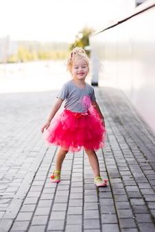 Jeune fille en élégante jupe rose marchant dans les escaliers