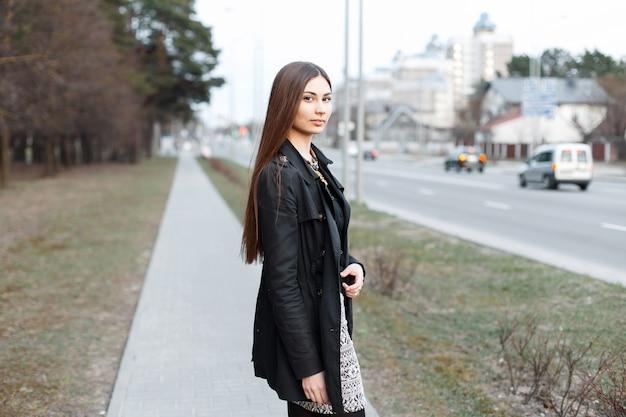 Jeune fille élégante marchant le long d'un chemin près de la ville