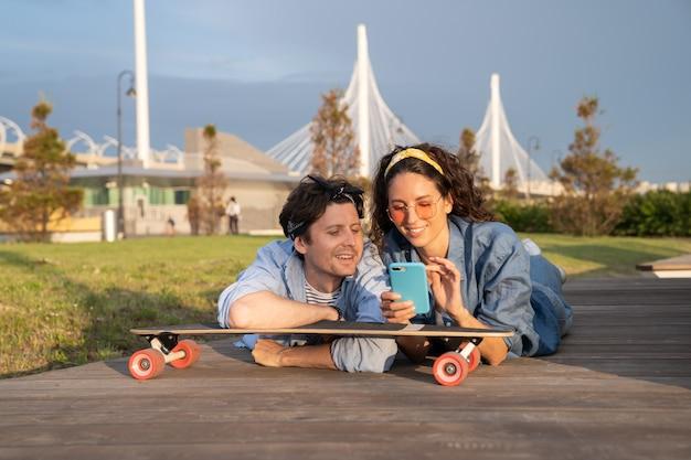 Jeune fille élégante montrer un message texte sur un smartphone allongé sur un longboard dans un parc urbain à l'extérieur