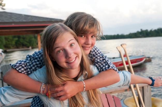 Jeune fille embrassant sa sœur aînée au lac des bois, en ontario