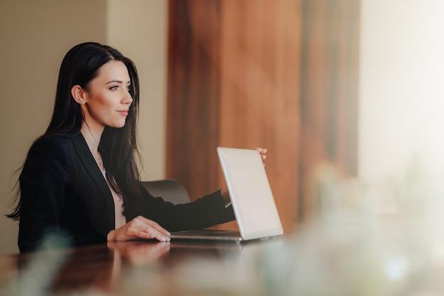 Jeune fille émotive attrayante dans les vêtements de style d'affaires assis à un bureau sur un ordinateur portable et un téléphone dans le bureau ou l'auditorium