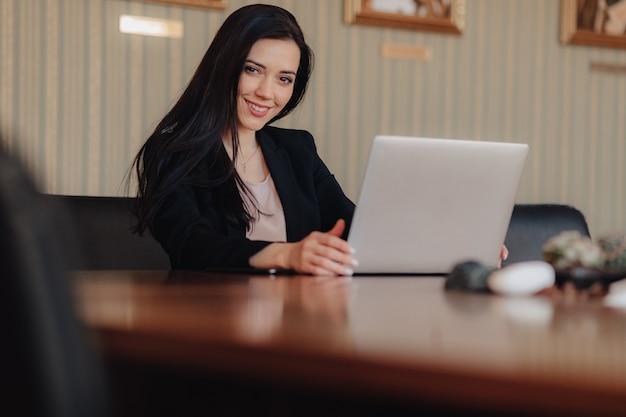 Jeune fille émotive attrayante en vêtements de style d'affaires assis à un bureau sur un ordinateur portable et un téléphone au bureau ou à l'auditorium