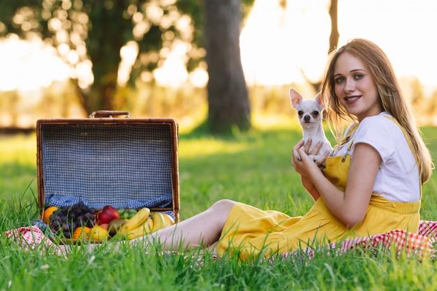 Jeune fille enceinte lors d'un pique-nique au coucher du soleil. avec chien chihuahua
