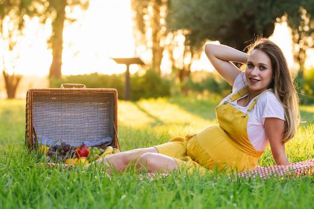 Jeune fille enceinte lors d'un pique-nique au coucher du soleil. se sentir bien