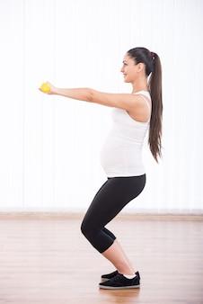 Jeune fille enceinte s'accroupit avec des haltères.